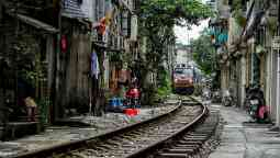 Train crossing the middle of Hanoi city with crowded houses