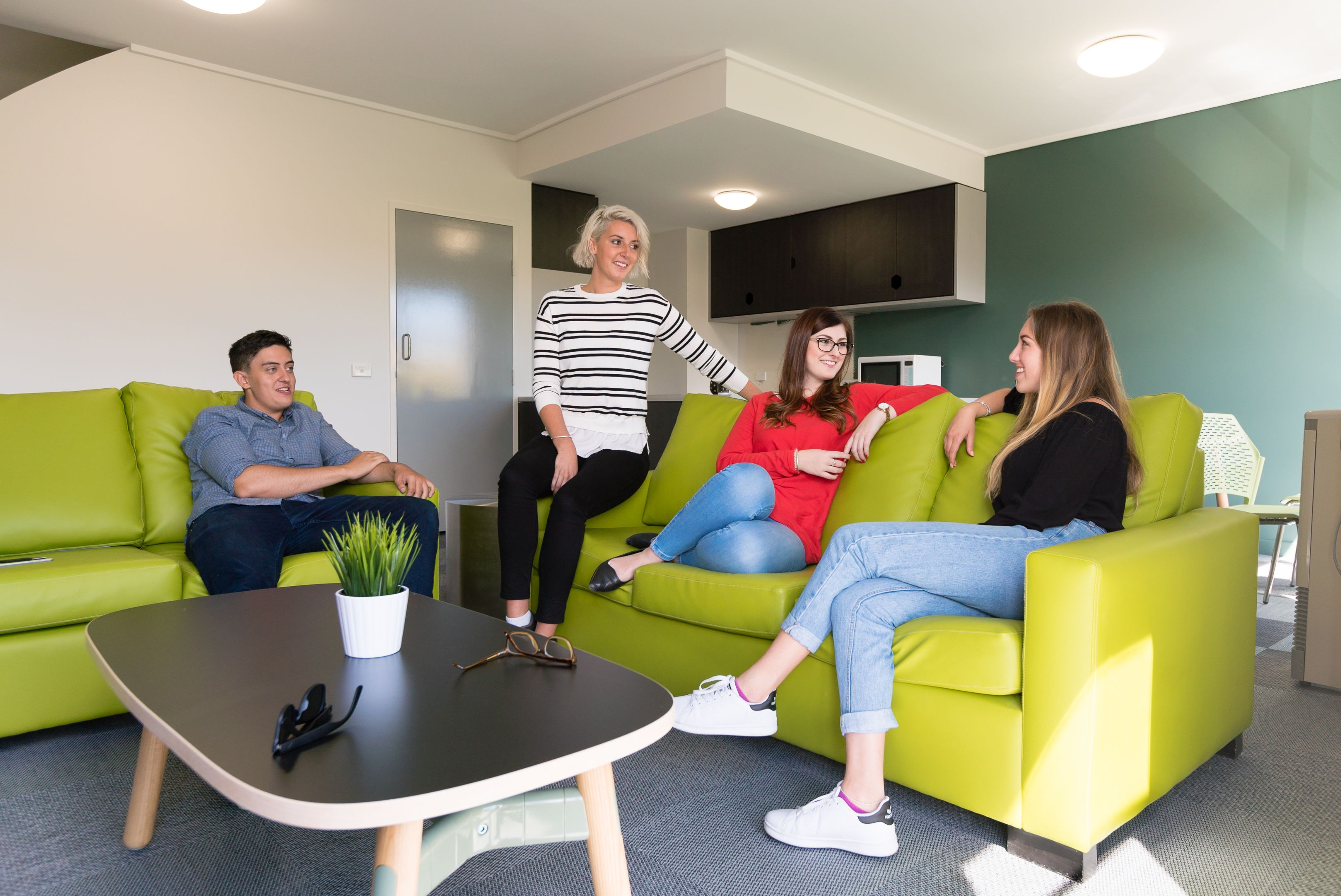 Four students socialise and sit on the couches within their student apartment